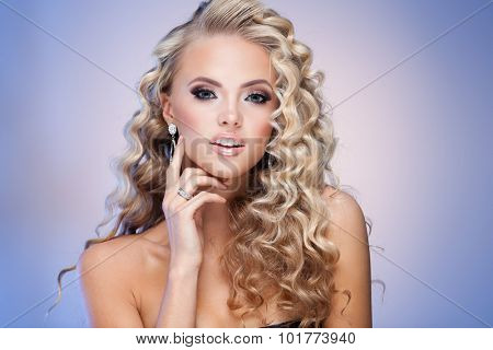 Young lady with luxury accessories on blue background