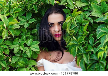 charming woman in green leaves