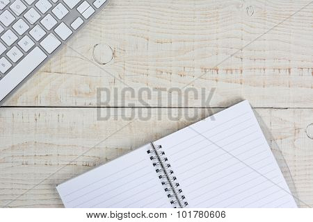 Overhead view of a blank note pad and a computer keyboard on a white wood table. Business desk mock up with copy space.