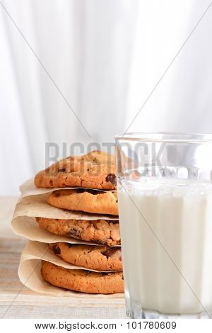 Closeup of a stack of fresh baked chocolate chip cookies and a glass of milk. Vertical format with an out of focus background and copy space.