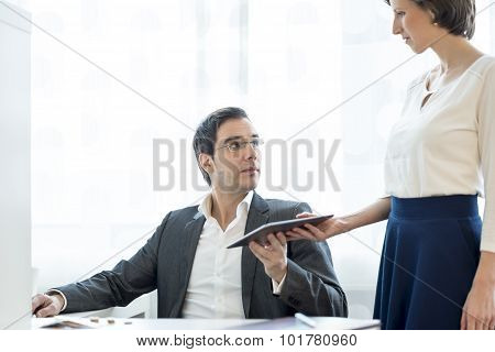Business Secretary Giving A Digital Tablet To Her Superior