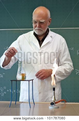 Teacher Mixes Chemicals In A Laboratory