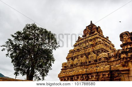 An ancient gopura of a temple against a cloudy sky