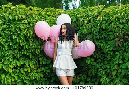 beautiful girl with balloons in green hedgerow