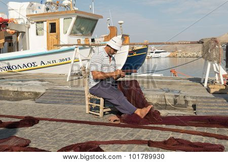 Paros, Greece 15 August 2015. Fisherman repairing the net at Paros island in Greece.