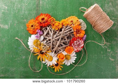 Fresh colorful flowers in shape of heart wooden table, closeup
