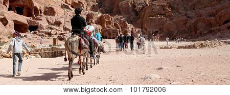 Tourists With Bedouins Visiting The Ancient Ruins Of Petra On Donkeys, Jordan
