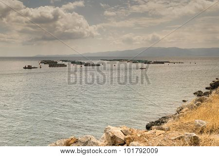 Fish farming in Greece against dramatic sky and clouds.