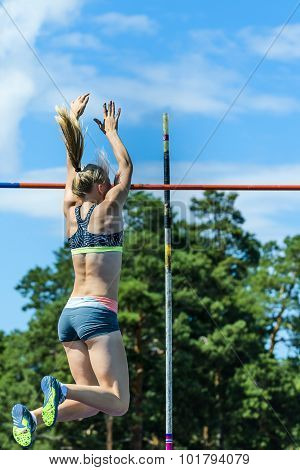 Girl athlete competing in the pole vault at a track and field competition