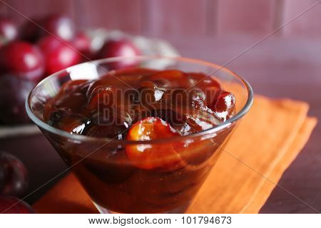 Tasty homemade plum jam in glass saucer on wooden table with napkin, closeup