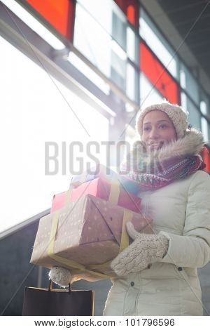 Smiling woman carrying stacked gifts during winter by window