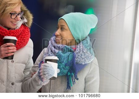 Happy women looking at each other while holding disposable cups