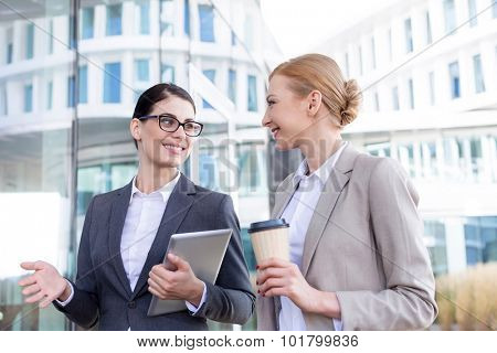 Happy businesswomen with tablet PC and disposable cup conversing outside office building