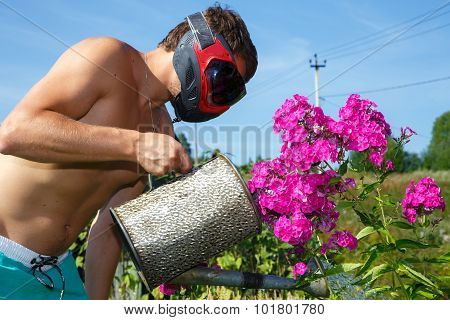 Man In Paintball Mask Watering The Flowers