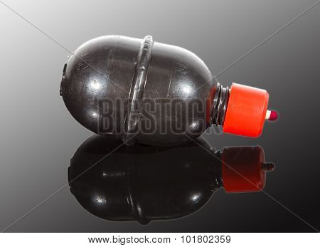 Paintball Grenade On Reflective Surface