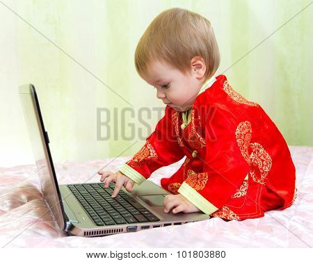 Baby Boy In New Year Suit With Computer Laptop