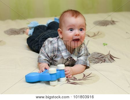 Funny Pleased Little Boy Lying On The Bed With His Toy