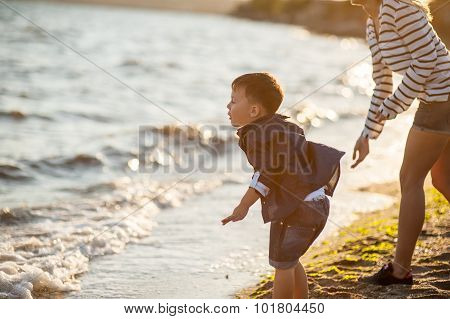 Beautiful boy with a woman relaxing on the beach.