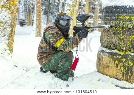 Paintball Player With Gun Behind Tires On Snow
