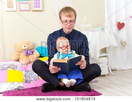 Serious Little Boy Read An Old Book With His Father In Glasses
