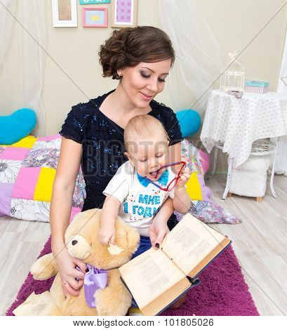Little Boy Together With His Mother And Teddy Bear Read A Book