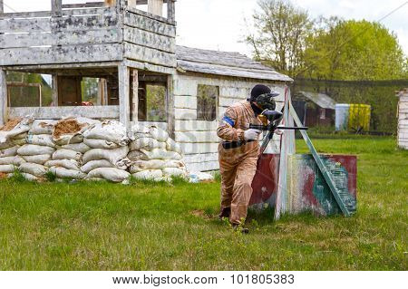 Paintball Warrior With Paint Gun And Fortress Behind