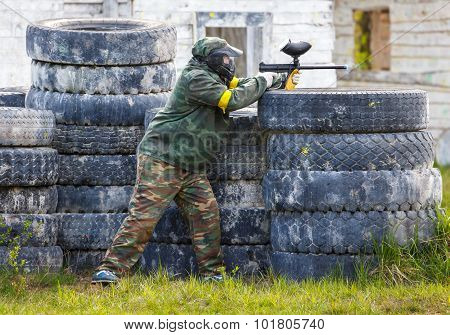 Paintball Sportsman Standing Behind Tires And Shooting