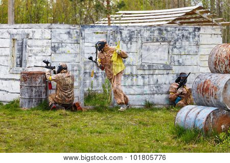 Three Men In Dynamic Situation With Paintball Flag