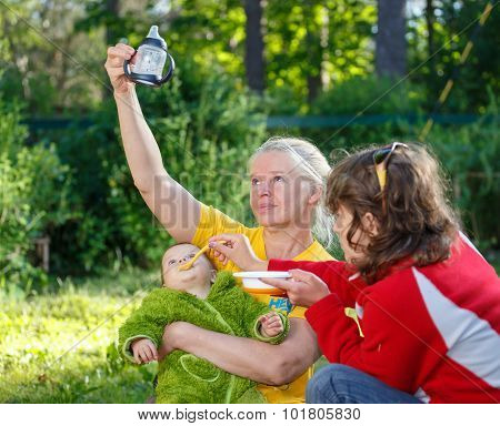 Funny Process Of Feeding Baby By Mom And Granny On The Grass