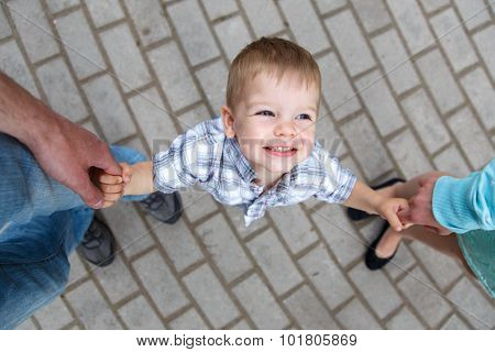 Happy Little Boy Holding Fingers Of Father And Mother