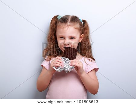 Cunning Kid Girl Eating Dark Chocolate With Curious Look