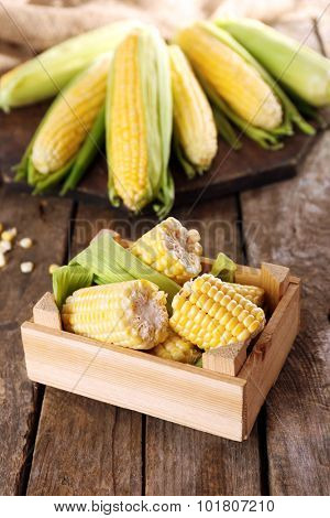 Fresh corn on cobs in crate on wooden table, closeup