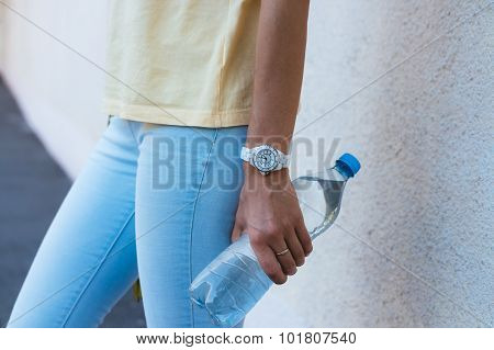 Bottle Of Drinking Water In A Female Hand Closeup