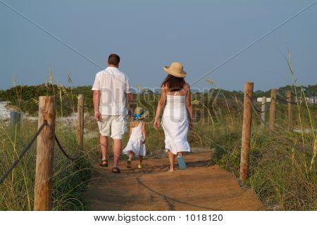 Family Walk Along The Boardwalk On The Beach