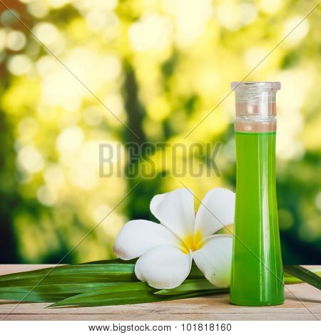 bottle of essential fragrant oil on wooden floor with pandan leaf and flower.