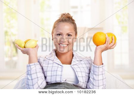Portrait Of Young Woman Holding Lemons In Hands