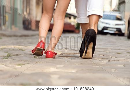 Mom In Black Shoes With Her Daughter In Red Shoes Go Off Together
