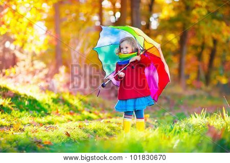 Child Playing In Autumn Rainy Park