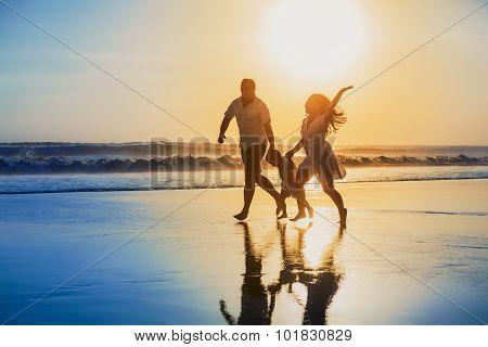 Positive Family Running With Fun On The Sunset Beach