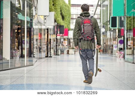 Young man, carrying a skateboard, walking casually through a modern shopping mall.