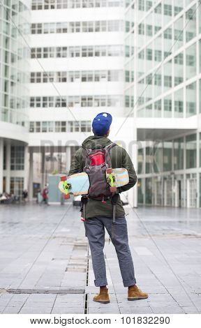 Skateboarder, with his skateboard tucked away in his backpack, looking at a tall, modern, office building