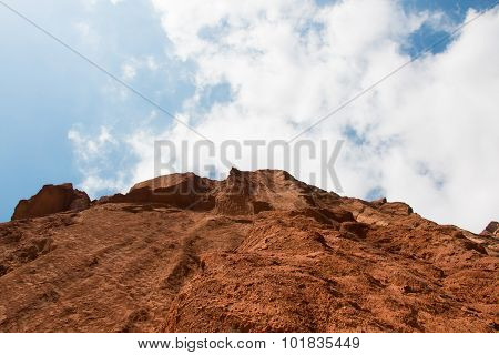 Steep Mountain And Cloudy Blue Sky