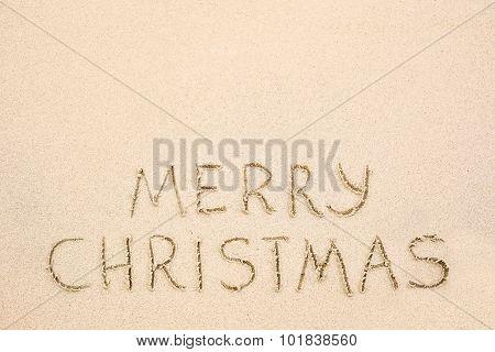 Merry Christmas Inscription On Wet Yellow Beach Sand