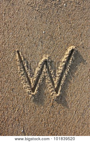 Alphabet's letter W handwritten in sand on the beach, at sunrise.