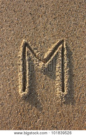 Alphabet's letter M handwritten in sand on the beach, at sunrise.