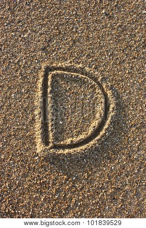 Alphabet's letter D handwritten in sand on the beach, at sunrise.