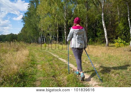 Young woman goes Nordic walking outdoors. Back view