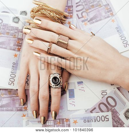 hands of rich woman with golden manicure and many jewelry rings on cash euros