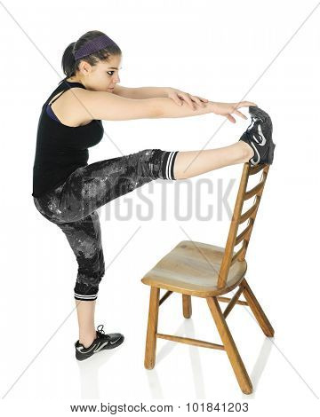 An attractive teen girl working out with one foot on the top of a ladder back chair while stretching to touch her toes.  On a white background.