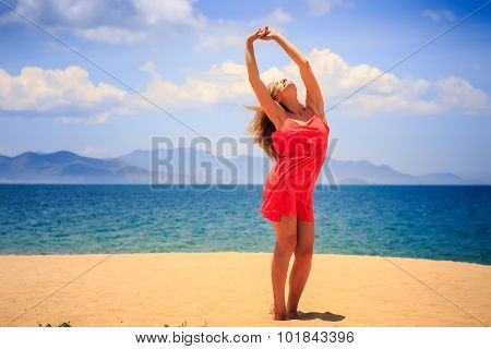 Blond Girl In Red Stands On Sand Lifts Hands Over Head